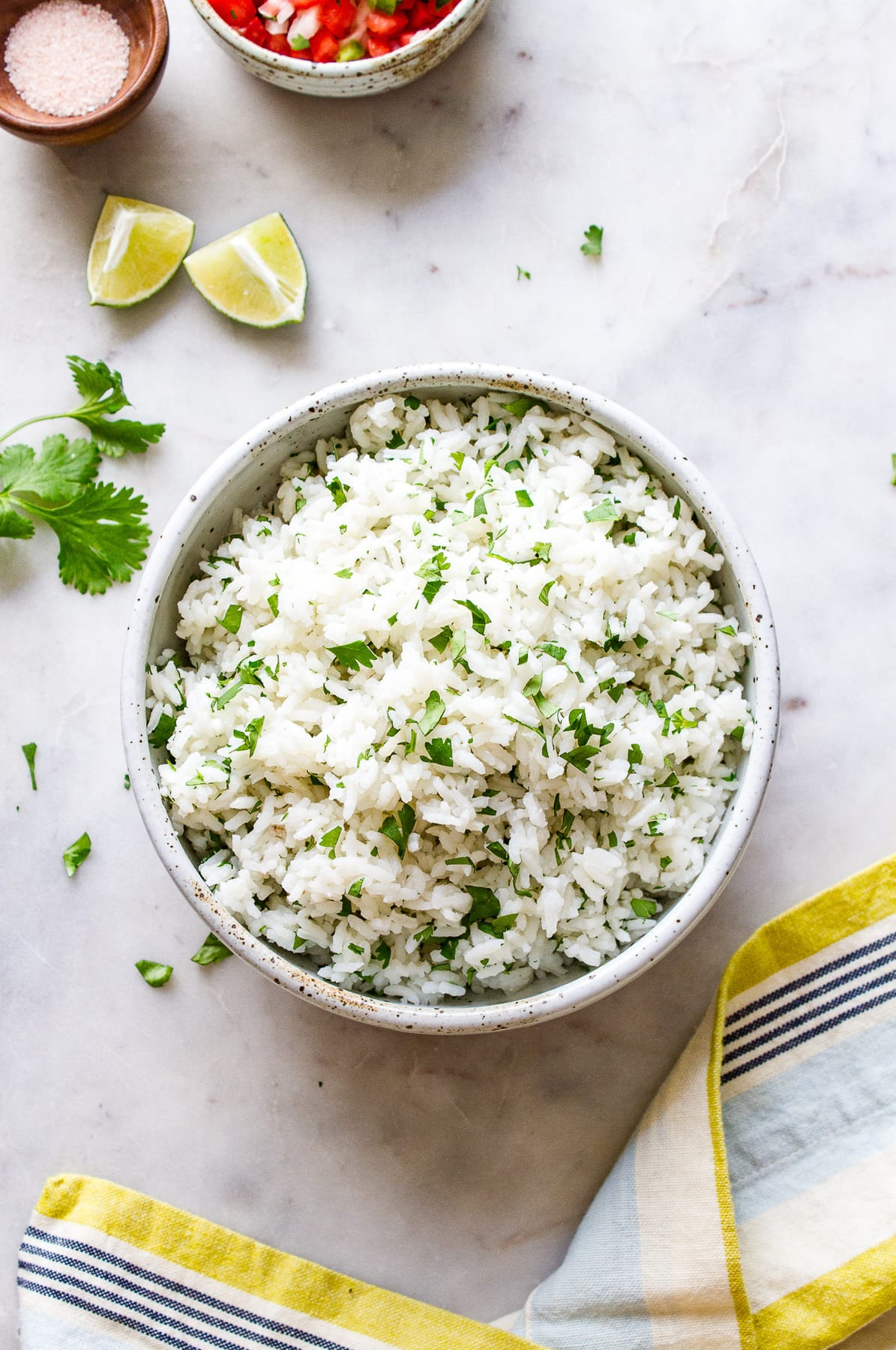 top down view of cilantro lime rice in a serving bowl with items around.