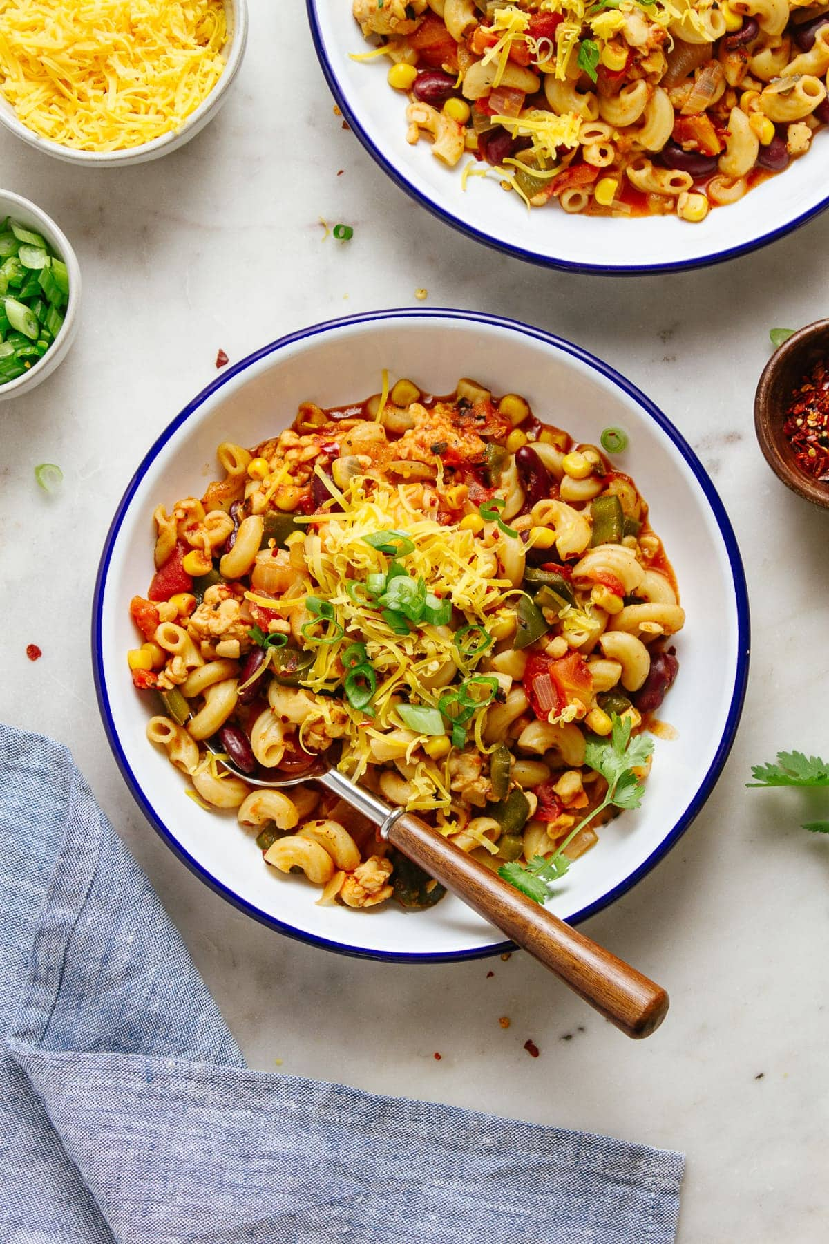top down view of a serving of vegan chili mac in a white bowl with blue rim.