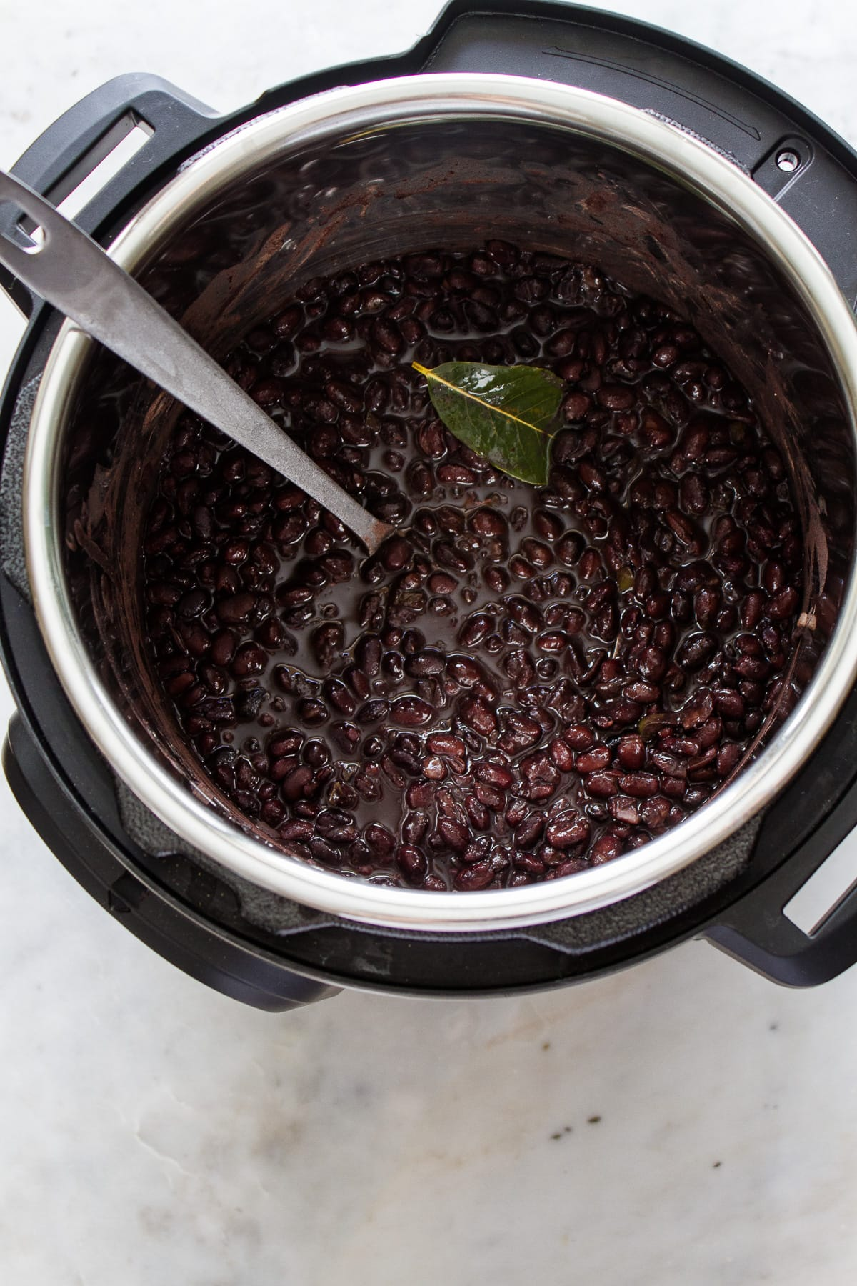 top down view of freshly cooked instant pot black beans in an instant pot with ladle.