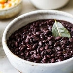 side angle view of easy instant pot black beans in a serving bowl with items surrounding.
