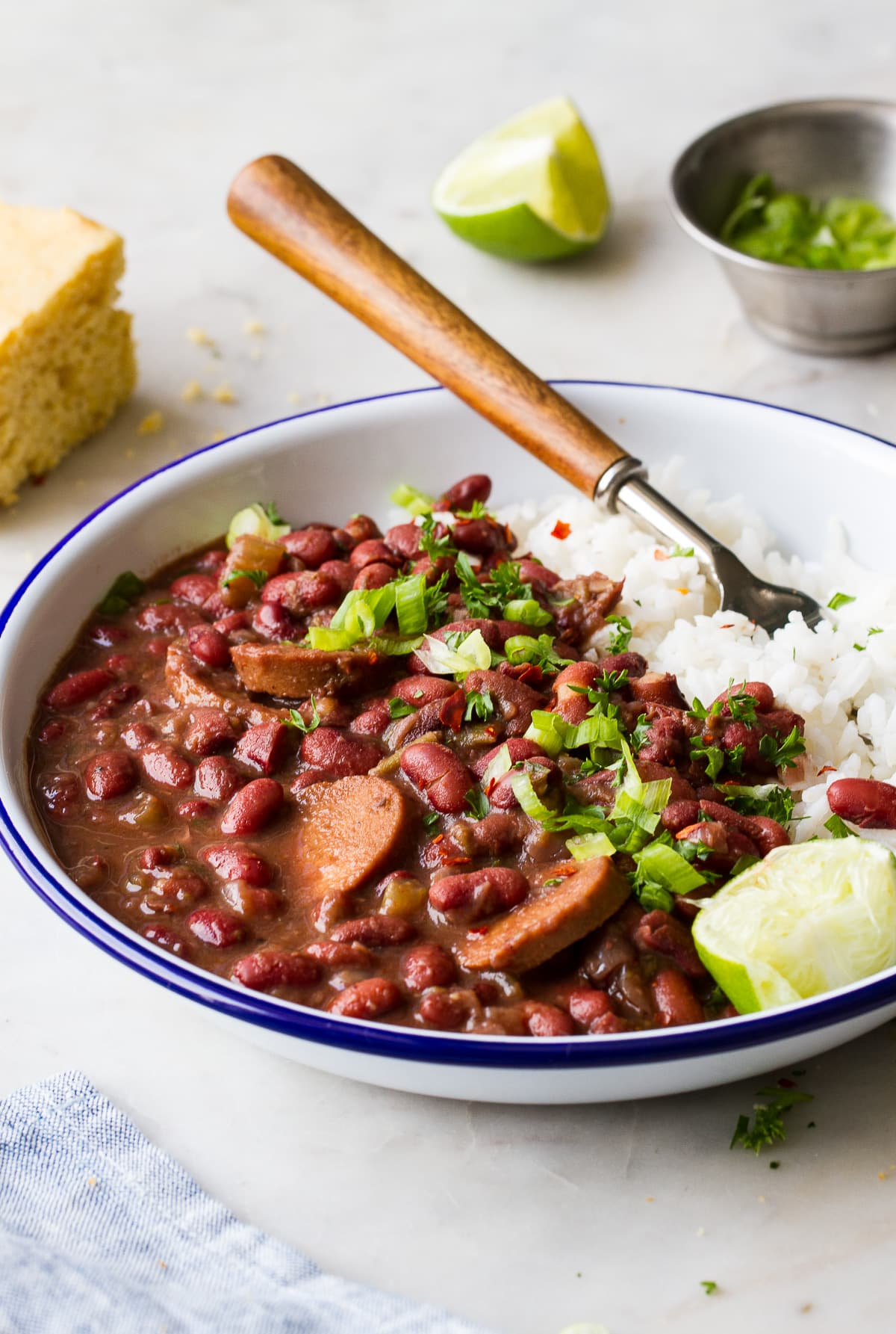 side angle view of a white bowl with blue rim filled with a serving of vegan red beans and rice.