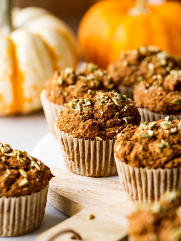 head of view of freshly made vegan pumpkin muffins resting on a serving board.