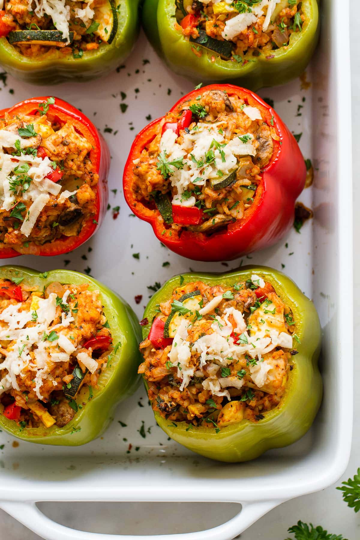 top down view of vegan stuffed bell peppers freshly baked in a baking dish.