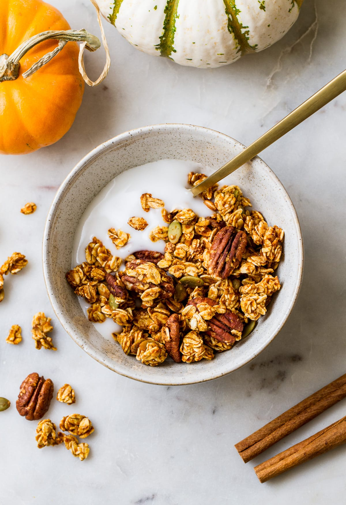 top down view of a bowl with a serving of coconut yogurt and pumpkin granola with a gold spoon surrounded by items.