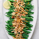top down view of healthy, vegan green beans almondine on a serving platter.