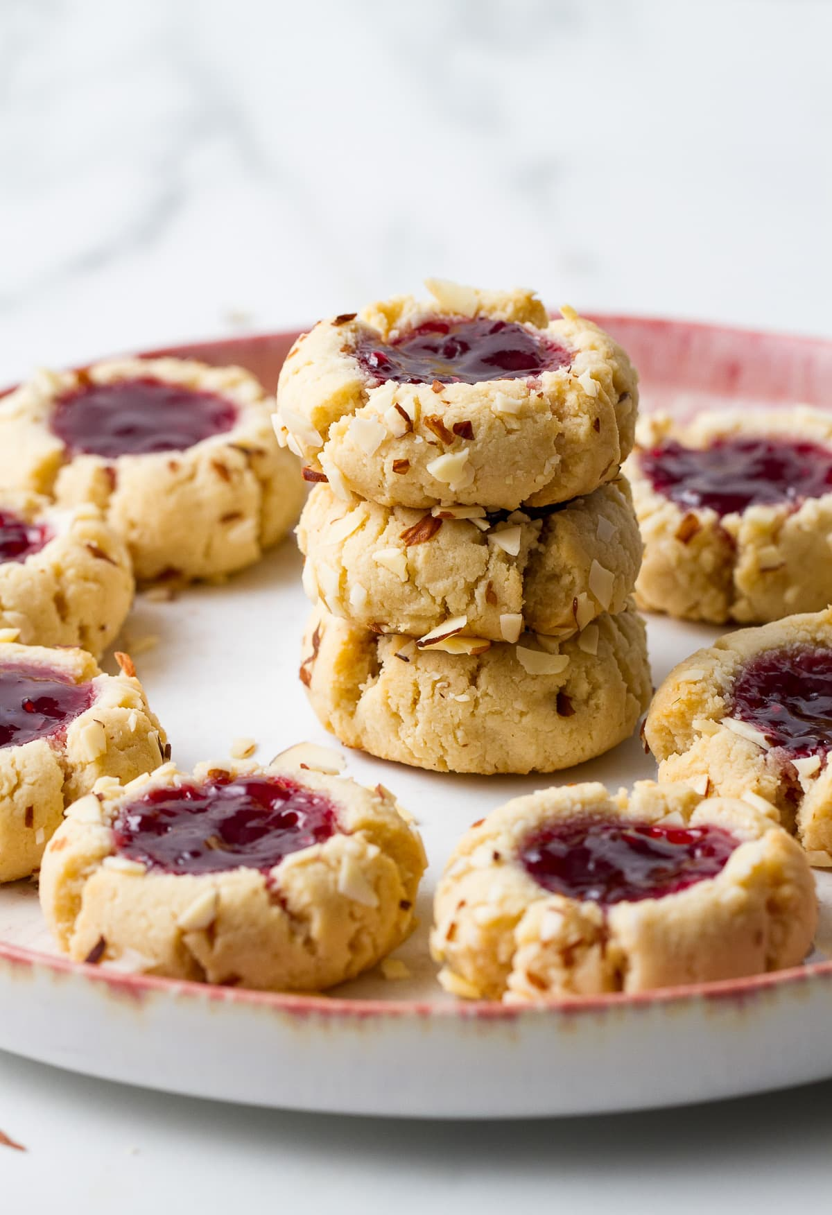 head on view of 3 stacked almond thumbprint cookies surrounded by more cookies.