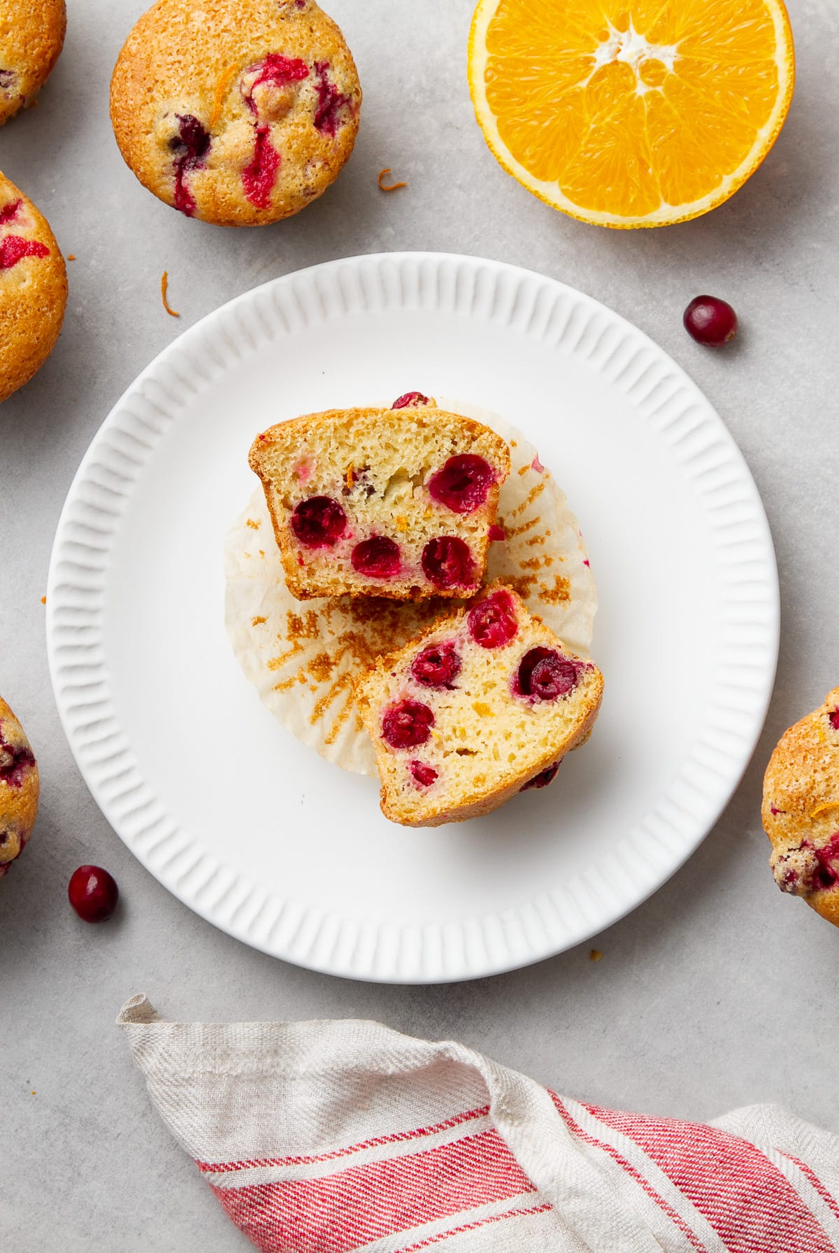 top down view of cranberry orange muffin sliced in half on a small white plate.