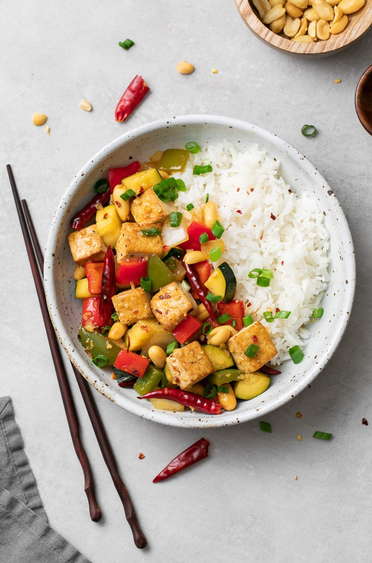 top down view of a serving of kung pao tofu and rice in a bowl with things surrounding.