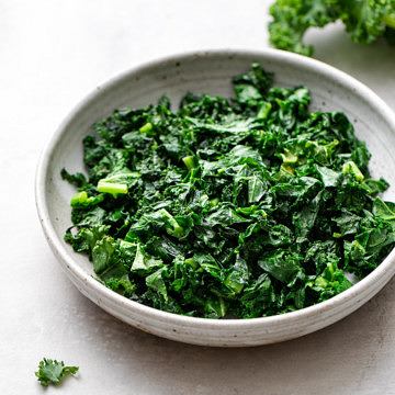 side angle view of sauteed kale in a bowl.