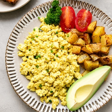 side angle view of a small plate with tofu scramble and items surrounding.