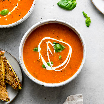 top down view of bowl with serving of tomato basil soup and items surrounding.