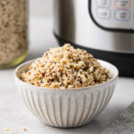 head on view of a bowl filled with quinoa made in an instant pot with items surrounding.