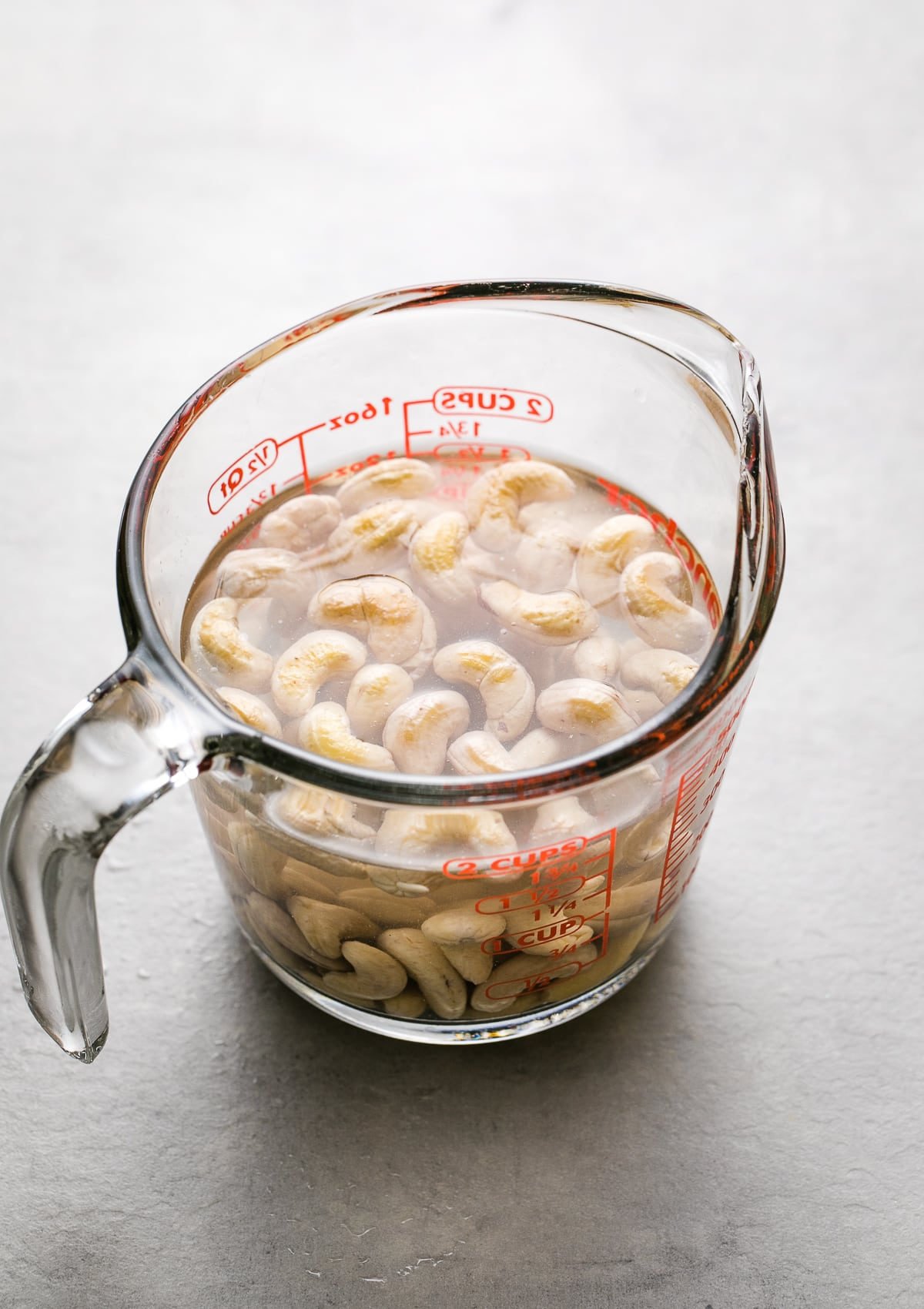 side angle view of cashews soaking in water in a glass measuring cup.