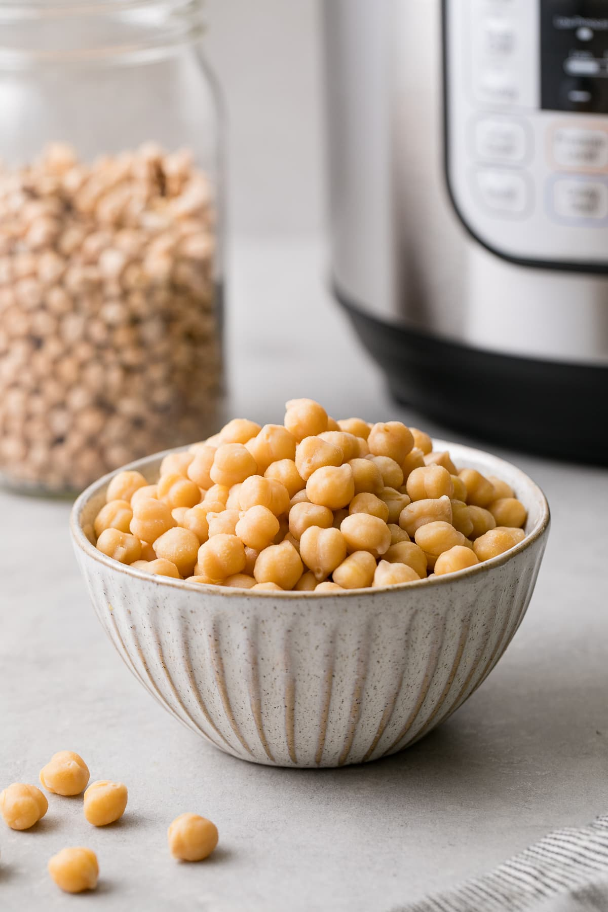 head on view of freshly cooked instant pot chickpeas in a small bowl with items surrounding.
