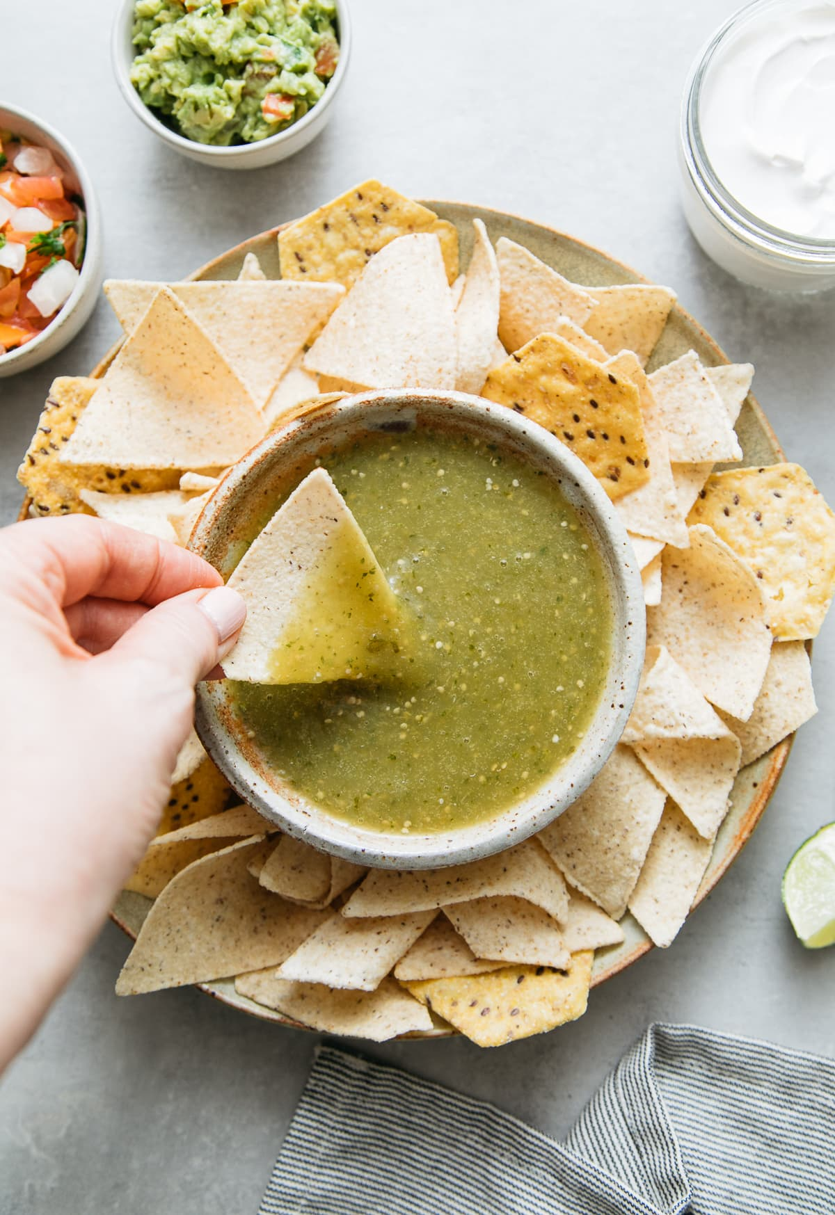 top down view of chip being dipped into bowl filled with tomatillo verde sauce surrounding by tortilla chips and other items.