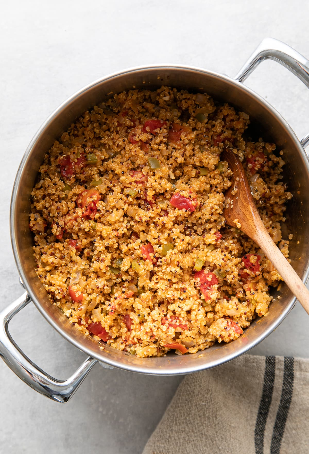 top down view of pot with freshly made quinoa Spanish rice with wooden spoon.