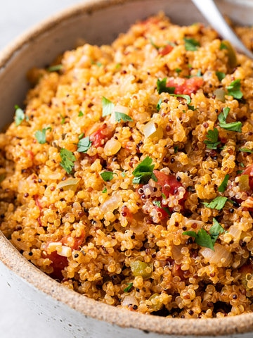 up close, side angle view of healthy quinoa Spanish rice in a serving bowl.