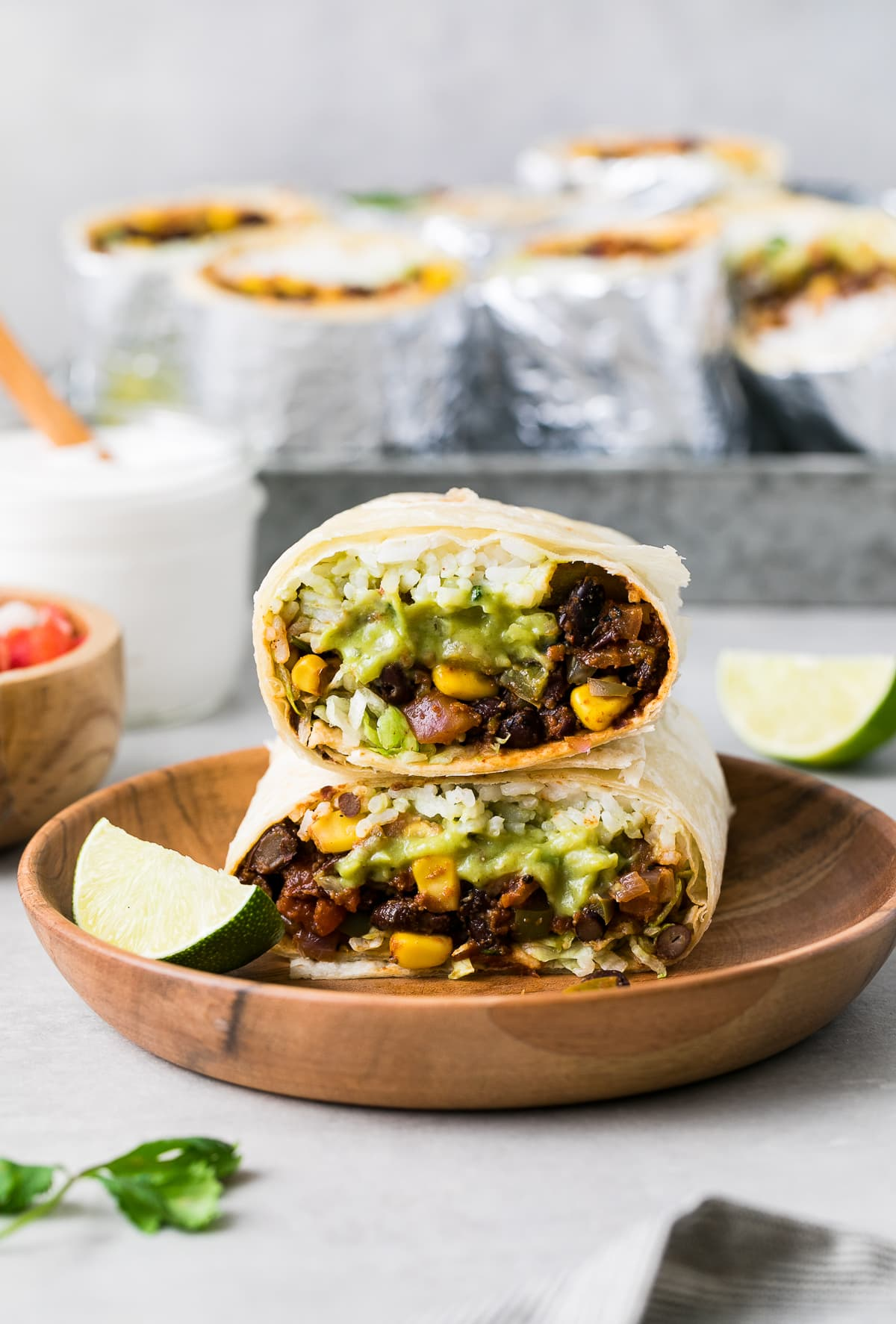 head on view of 2 halves of vegan burrito stacked on each other with items surrounding.