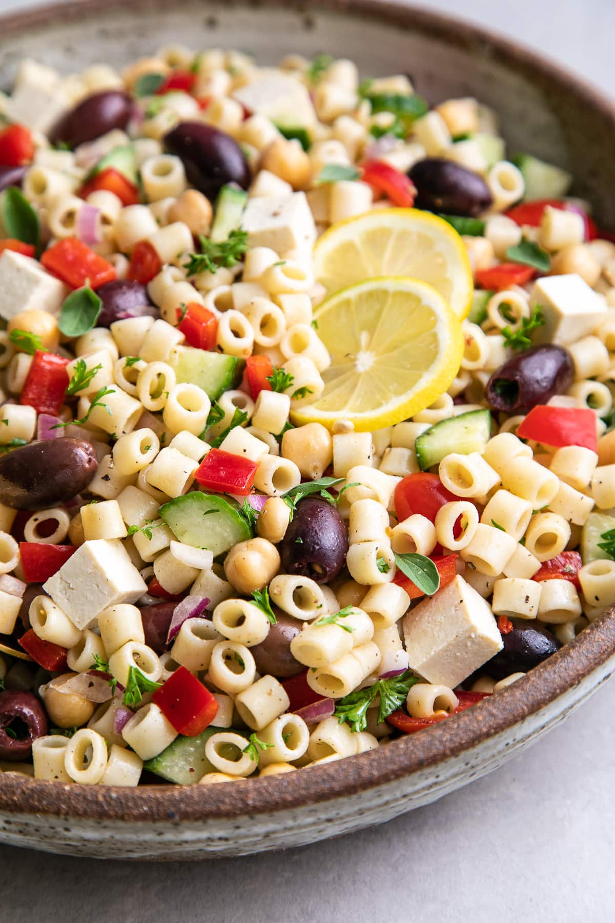 side angle view of healthy, vegan Greek pasta salad in a serving bowl with gold serving spoon.