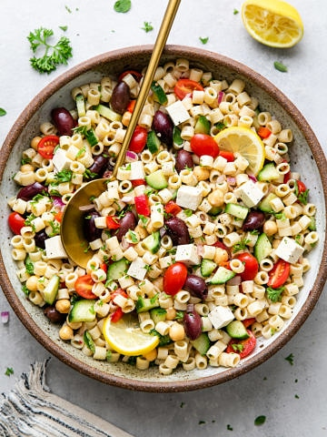 top down view of healthy, vegan Greek pasta salad in a serving bowl with gold serving spoon.