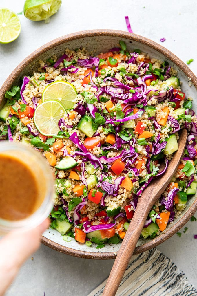 top down view of Thai quinoa salad with almond dressing about to poured overtop.