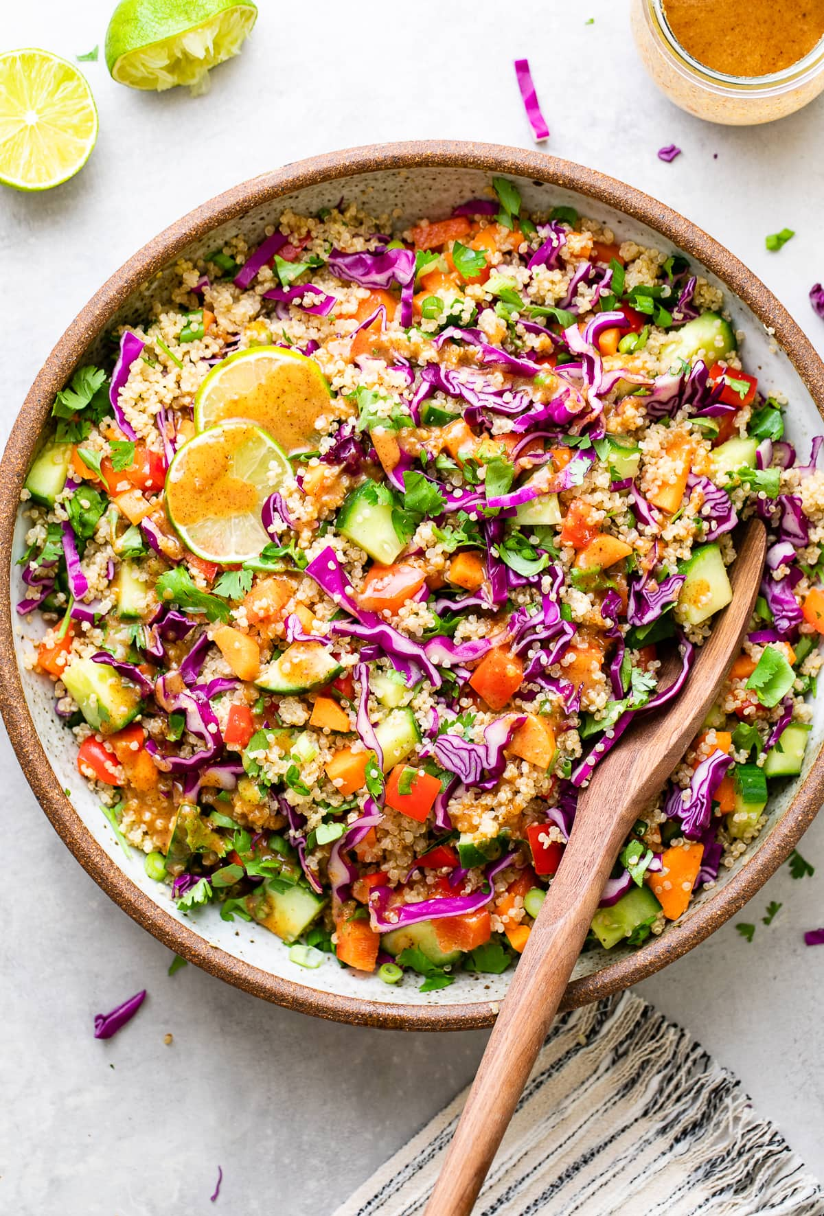top down view of healthy Thai quinoa salad in a bowl with serving spoon.