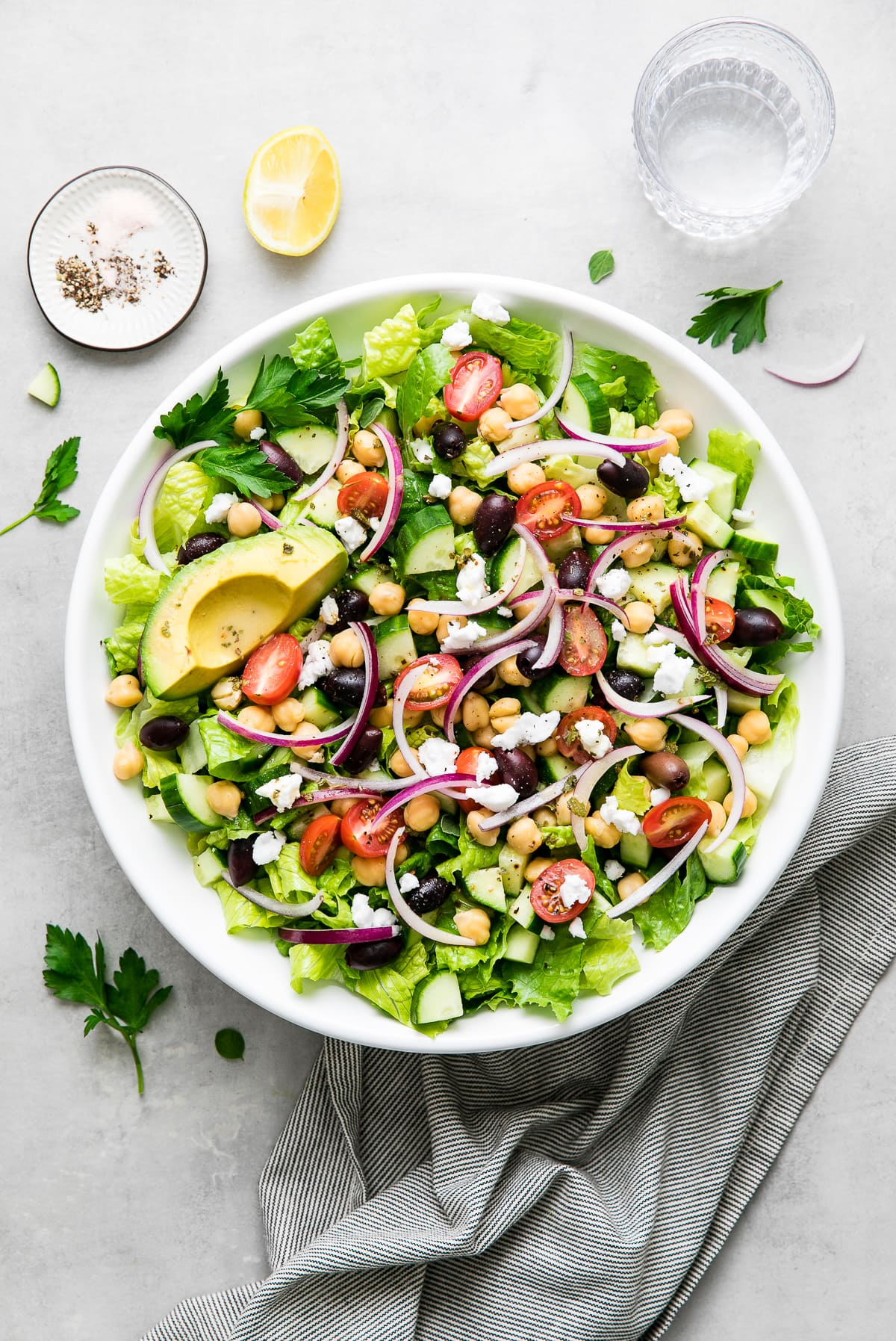 up close, top down view of mediterranean chop salad in a white bowl with items surrounding.
