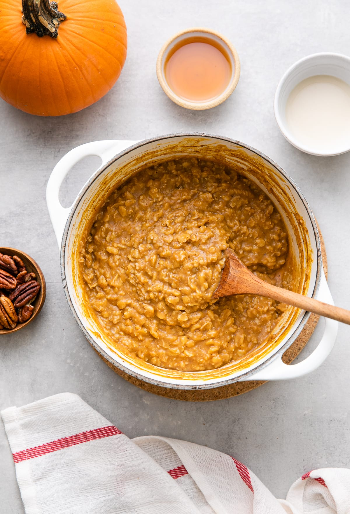 top down view of freshly made batch of the best pumpkin oatmeal in a pot with items surrounding.