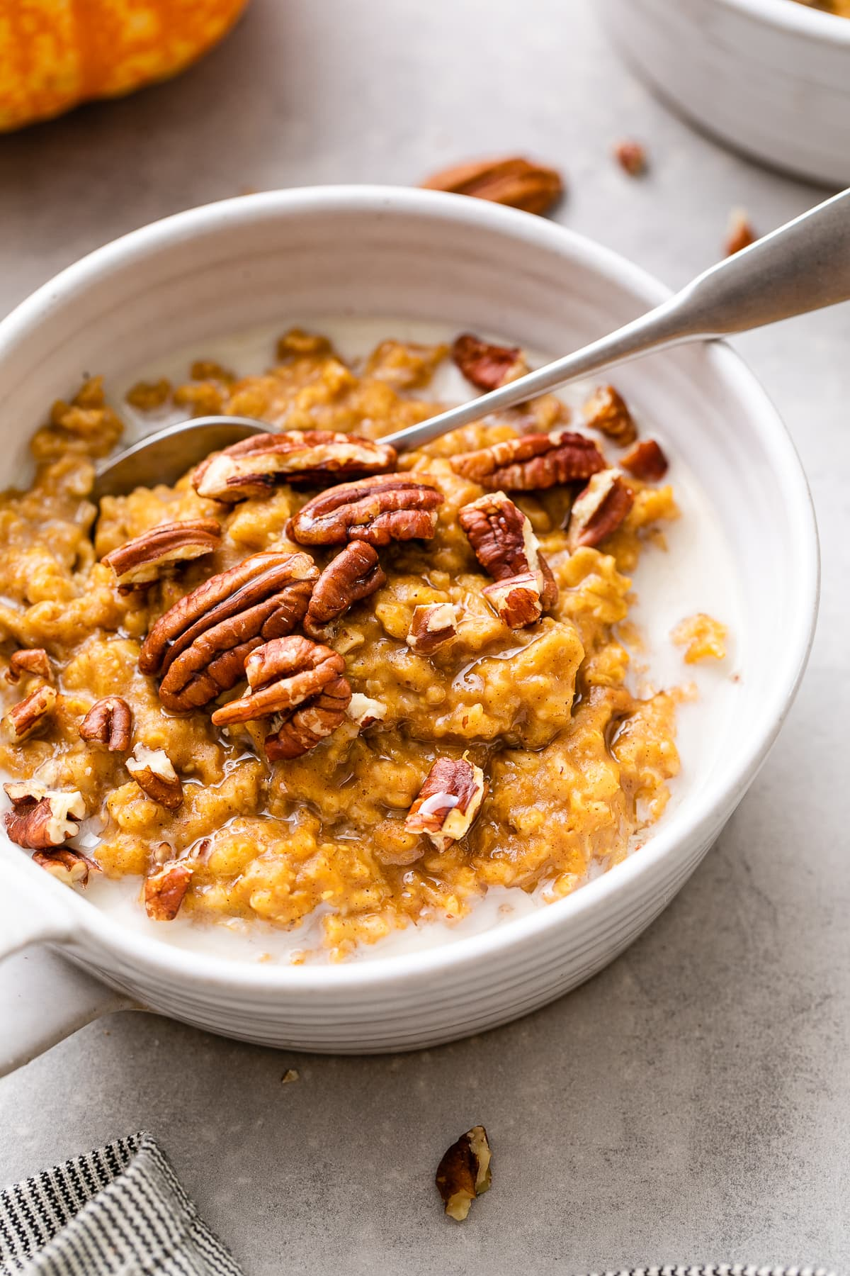 side angle view of vegan pumpkin oatmeal in a whole bowl with spoon and items surrounding.