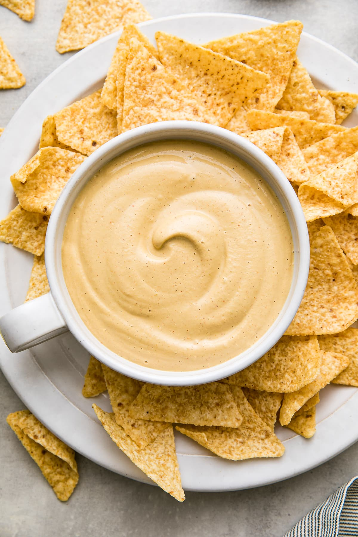 top down view of bowl of freshly made vegan queso in a bowl with chips surrounding.