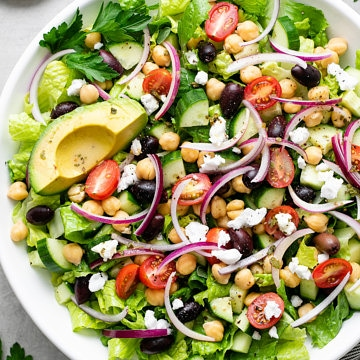 top down view of mediterranean chop salad in a white bowl with items surrounding.