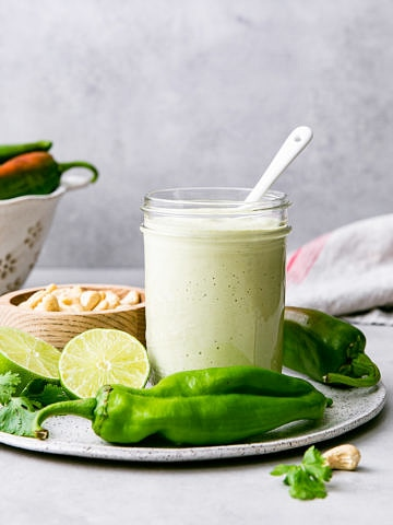 head on view of mason jar with creamy hatch chile dressing and items surrounding.