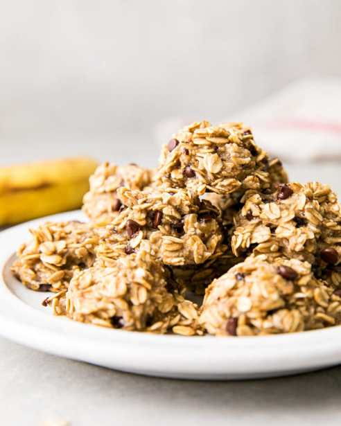 side angle view of group of stacked banana oatmeal chocolate chip cookies on a white plate with items surrounding.