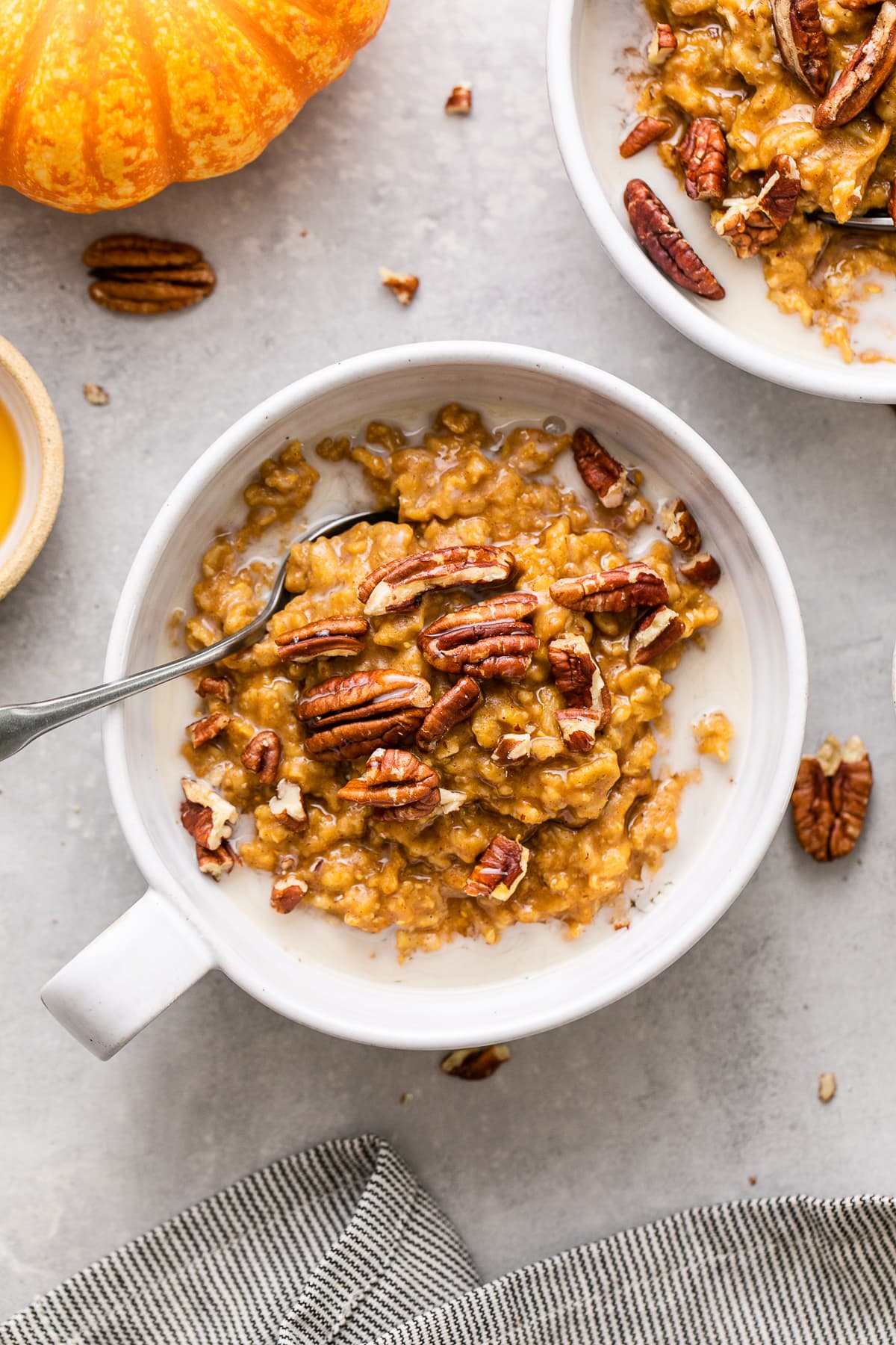 top down view of healthy pumpkin oatmeal in a whole bowl with spoon and items surrounding.