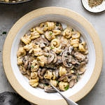 top down view of bowl with serving of vegan mushroom stroganoff with fork and items surrounding.