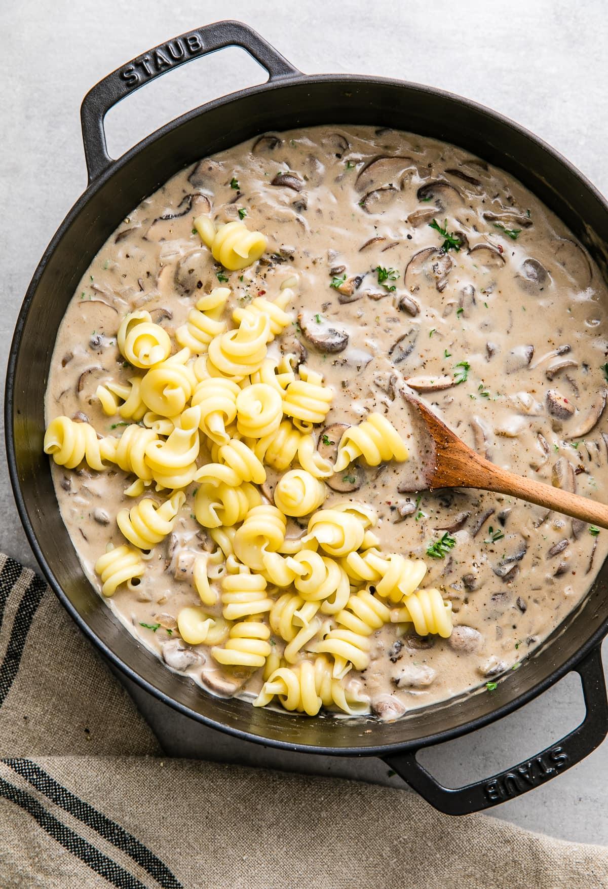 top down view of pasta added to creamy vegan mushroom stroganoff in a black pot.