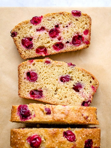 top down view of sliced cranberry orange bread on parchment paper.