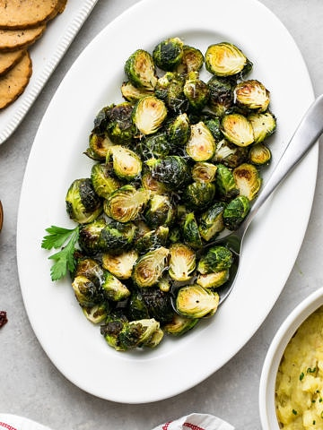 top down view of serving platter with roasted brussels sprouts with items surrounding.