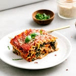 side angle view of slice of vegan lasagna on a plate with items surrounding.