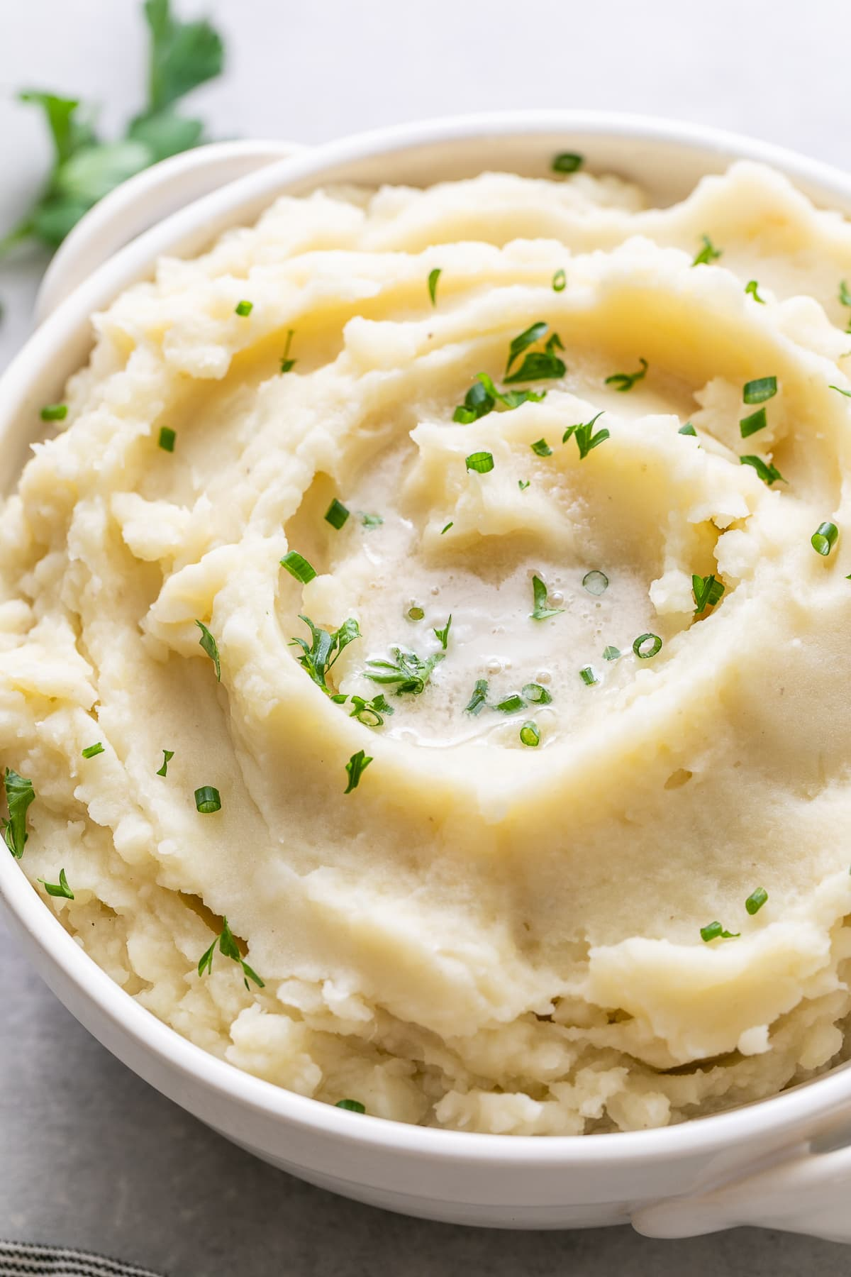 side angle view of vegan mashed potatoes in a serving bowl.