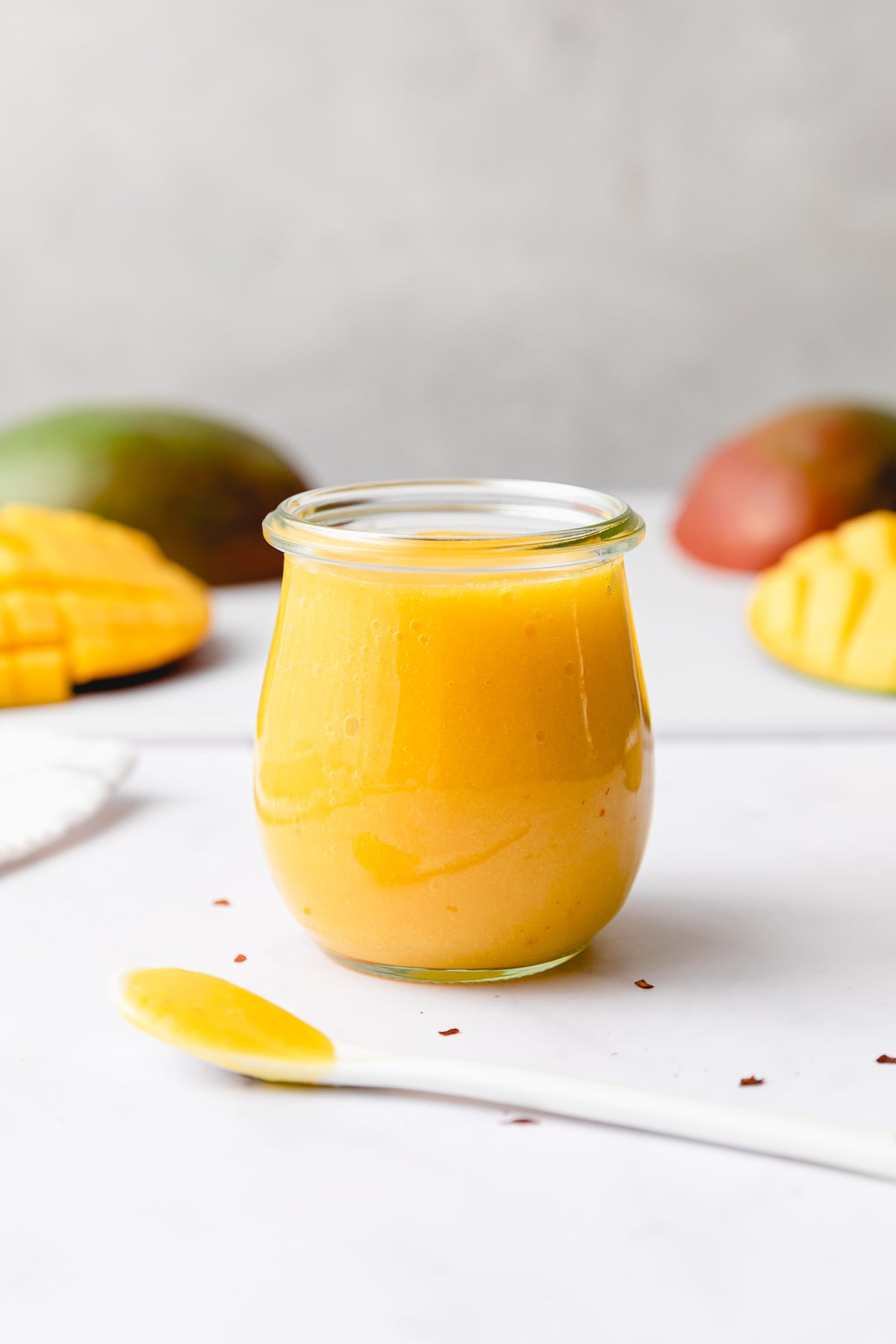 head on view of mango dressing in a glass jar with items surrounding.