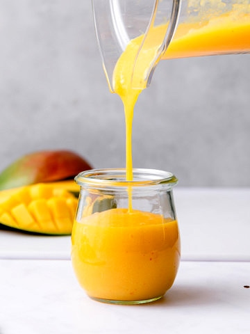 head on view of spicy mango dressing being poured into a glass jar.