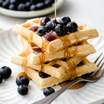 head on view of easy vegan waffles with blueberries and syrup.