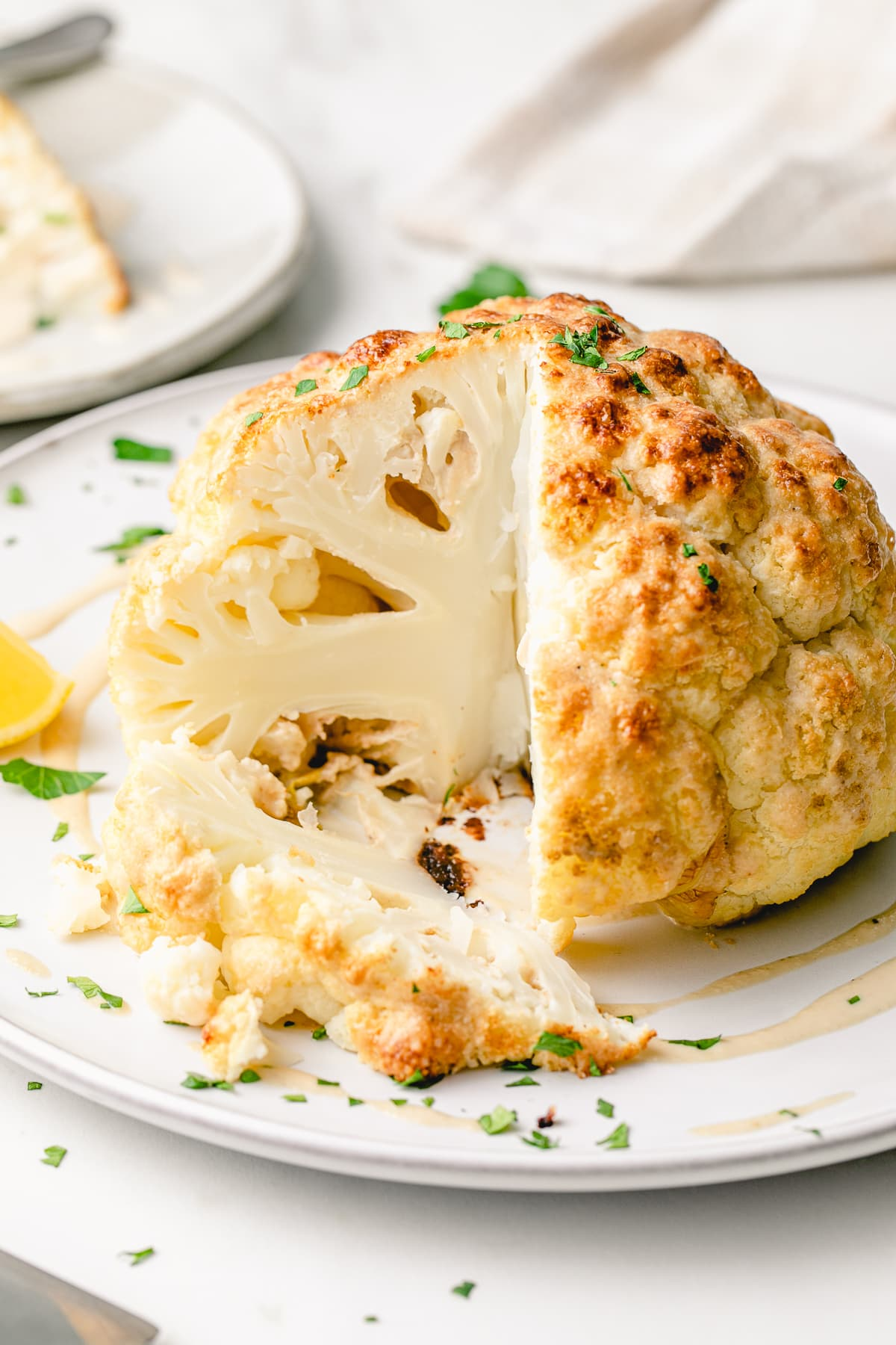 head on view of whole roasted cauliflower with slice cut on a serving platter and items surrounding.