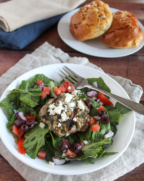 spinach feta turkey burger served on top of a salad