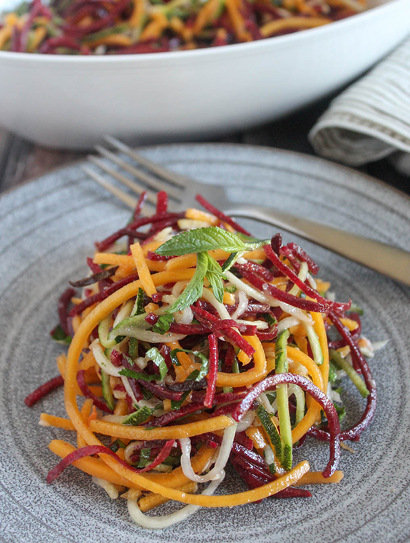 spiralized vegetables on a plate topped with fresh mint