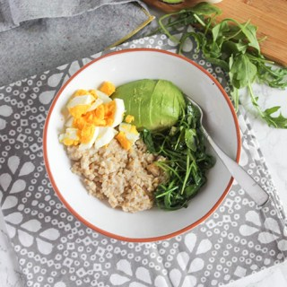 savory breakfast bowl filled with oats greens egg and avocado