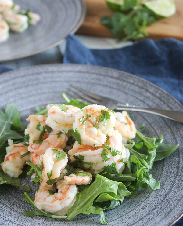 cilantro lime shrimp on top of baby arugula on a plate