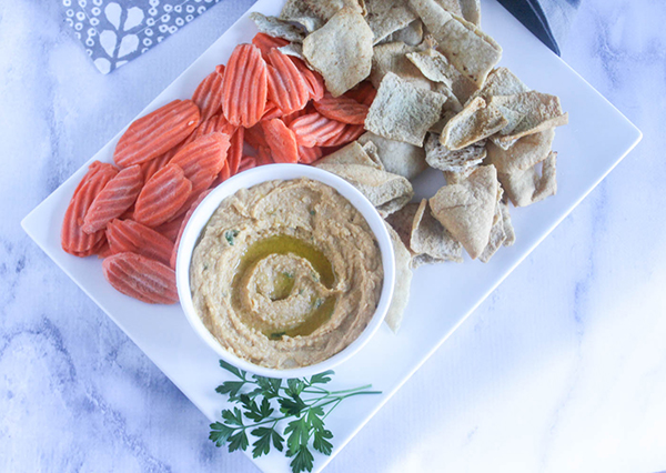 an overhead view of hummus in a bowl with pita chips and carrot chips