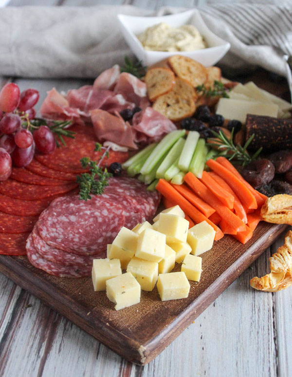 cheese cubes, salami, pepperoni, procsuitto, carrots celery and crackers on a board